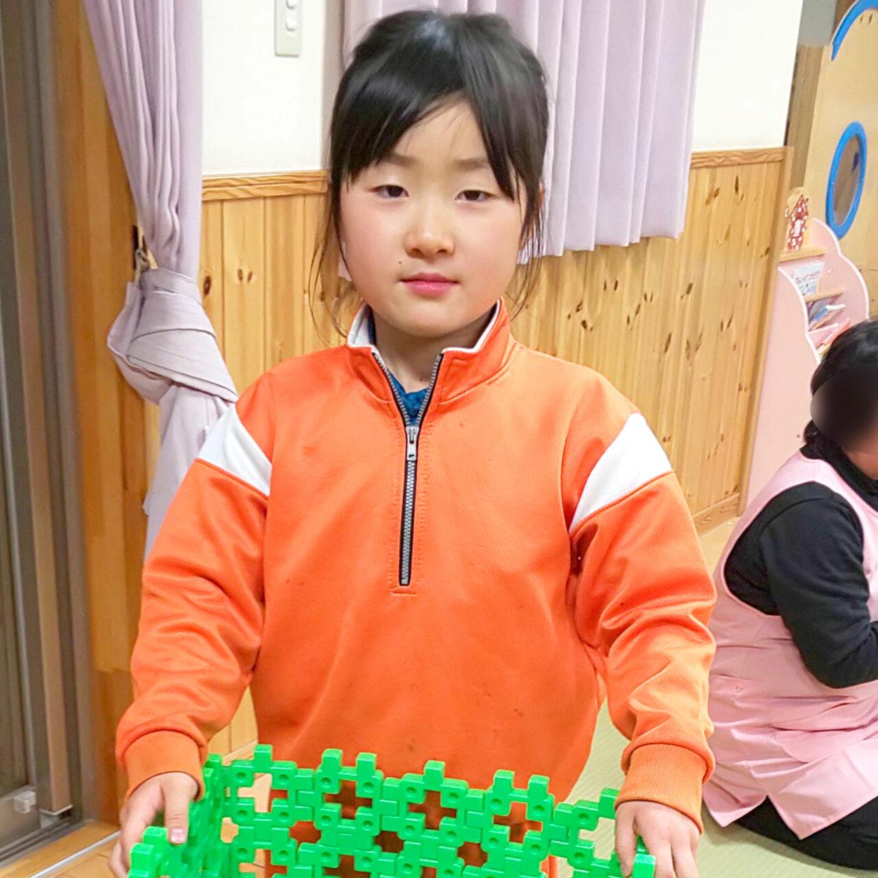 オレンジのジャージを着ておもちゃを抱える小倉美咲(小学三年生)。