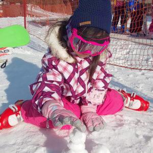 ピンク色の防寒着とゴーグルをして雪景色の中、雪遊びする小倉美咲(おぐらみさき)。
